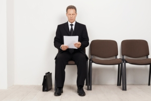 Ready for interview. Thoughtful senior man in formalwear holding paper while sitting at the chair in waiting room